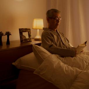 ベッドで本を読むシニア男性の写真素材 [FYI02937045]
