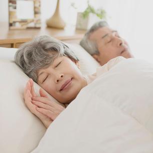 ベッドで眠るシニア夫婦の写真素材 [FYI02937050]