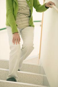 階段で膝を押さえるシニア女性の写真素材 [FYI02937054]