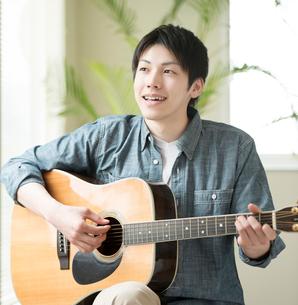 リビングでギターを弾く男性の写真素材 [FYI02937081]