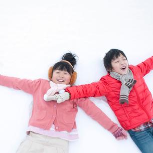 雪原に寝転ぶ子供たちの写真素材 [FYI02937222]