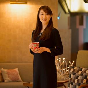 コーヒーカップを持ち微笑む女性のポートレートの写真素材 [FYI02937249]