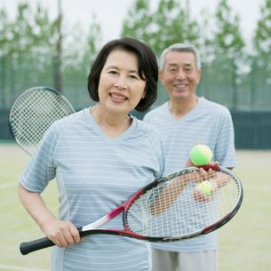 テニスラケットを持ち微笑むシニア夫婦の写真素材 [FYI02937338]