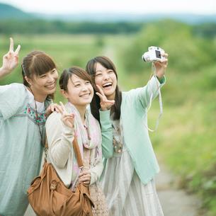 カメラで写真を撮る3人の女性の写真素材 [FYI02937376]