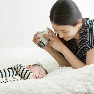 眠る赤ちゃんと見守る母親の写真素材 [FYI02937465]