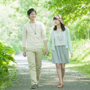 公園で手をつなぐカップルの写真素材 [FYI02937611]