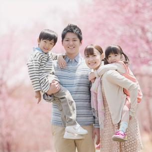 桜の前で微笑む家族の写真素材 [FYI02937778]