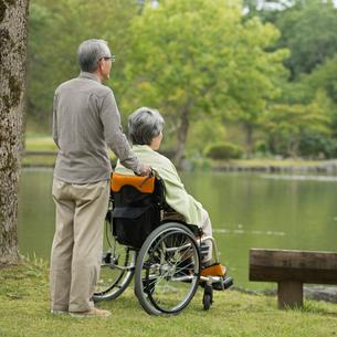 車椅子に乗り湖を眺めるシニア夫婦の後姿の写真素材 [FYI02937897]