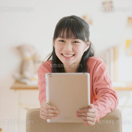 タブレットPCを持ち微笑む中学生の写真素材 [FYI02937900]