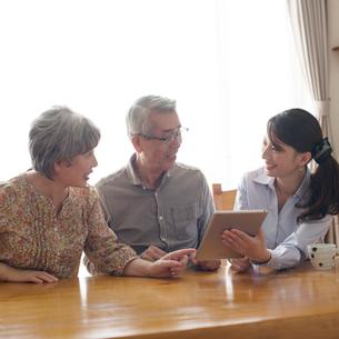 シニア夫婦を話をするケアマネージャーの写真素材 [FYI02938088]