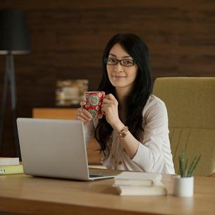 コーヒーカップを持ち微笑む女性の写真素材 [FYI02938090]