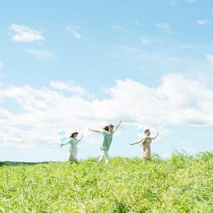 草原を走る3人の女性の写真素材 [FYI02938116]