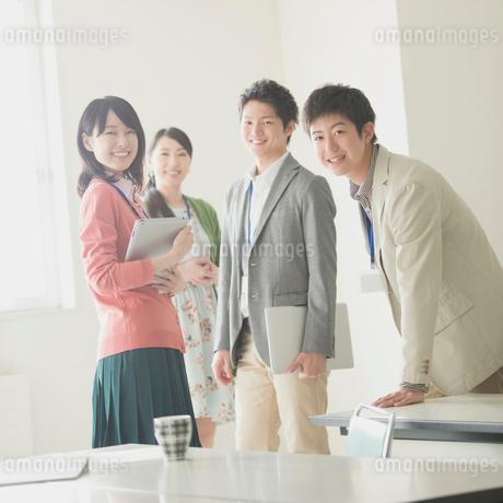 オフィスで微笑むビジネスマンとビジネスウーマンの写真素材 [FYI02938163]