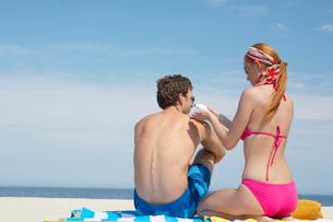 Woman applying sunscreen on mans backの写真素材 [FYI02938178]