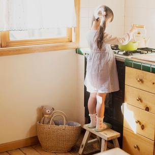 キッチンでお手伝いをする女の子の写真素材 [FYI02938215]