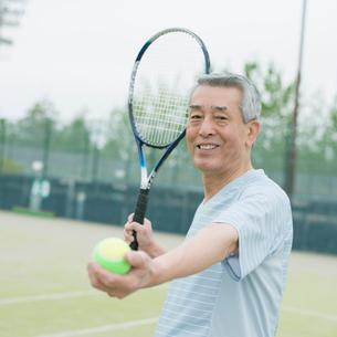 テニスラケットを持ち微笑むシニア男性の写真素材 [FYI02938226]
