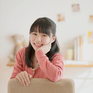椅子に座り微笑む中学生の写真素材 [FYI02938333]