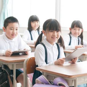 タブレットPCを持ち微笑む小学生の写真素材 [FYI02938534]