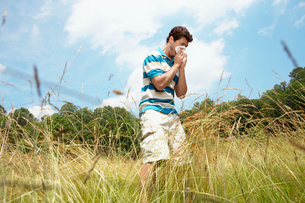 Man sneezing in field (low angle view)の写真素材 [FYI02938550]