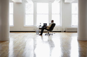 Man sitting at desk in empty officeの写真素材 [FYI02938612]