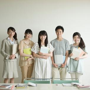 勉強道具を持ち微笑む学生と先生の写真素材 [FYI02938744]