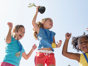 Girls celebrating medals and trophiesの写真素材 [FYI02938793]