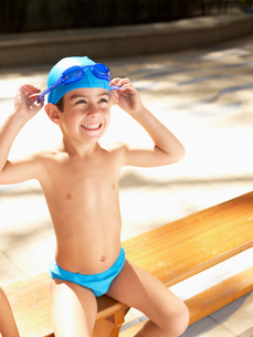 Boy in swimming trunks adjusting gogglesの写真素材 [FYI02938859]