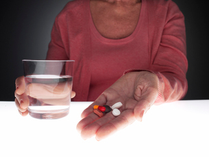 Woman holding pills and glass of waterの写真素材 [FYI02939022]