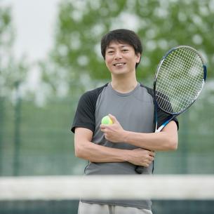 テニスラケットを持ち微笑むミドル男性の写真素材 [FYI02939075]