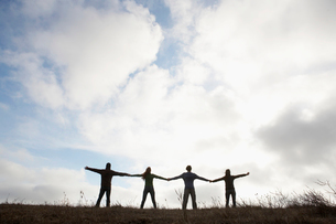 Four people holding hands in fieldの写真素材 [FYI02939150]