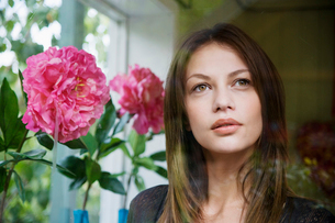 Young woman by pink flowers (portrait)の写真素材 [FYI02939183]