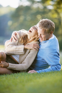 Couple lying on grass and laughingの写真素材 [FYI02939261]