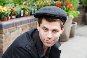 Young man wearing flat cap (portrait)の写真素材 [FYI02939267]
