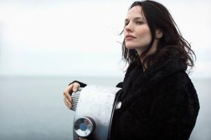 Young woman leaning on binocularsの写真素材 [FYI02939268]