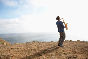 Man playing saxophone on cliffの写真素材 [FYI02939292]