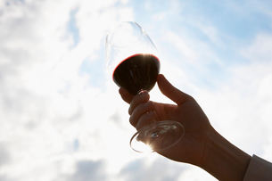 Person holding glass of red wineの写真素材 [FYI02939298]