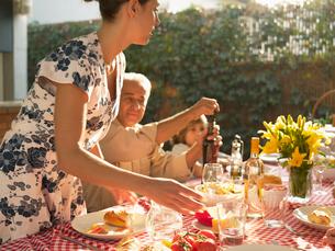 Family at dinner table in gardenの写真素材 [FYI02939325]