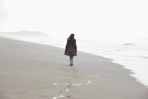 Woman walking on sandy beachの写真素材 [FYI02939357]