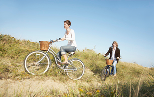 Couple cycling in fieldの写真素材 [FYI02939381]