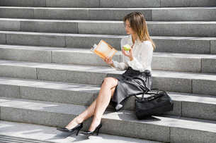 Young woman reading and eating on stepsの写真素材 [FYI02939464]