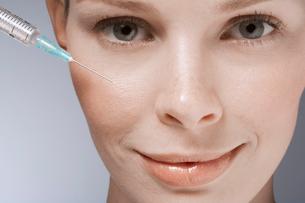 Syringe near womans faceの写真素材 [FYI02939536]