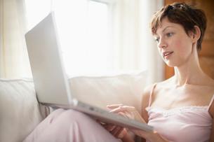 Woman using laptop computer on sofaの写真素材 [FYI02939546]