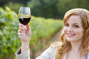 Young woman holding glass of red wineの写真素材 [FYI02939559]