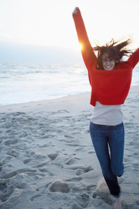 Young woman jumping on sandy beachの写真素材 [FYI02939621]