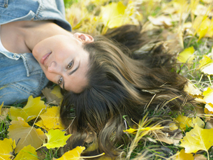 Woman lying on autumnal leavesの写真素材 [FYI02939643]
