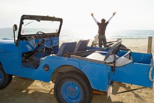 Man standing on beach near beach buggyの写真素材 [FYI02939652]