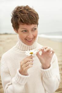 Woman pulling petals off daisyの写真素材 [FYI02939723]