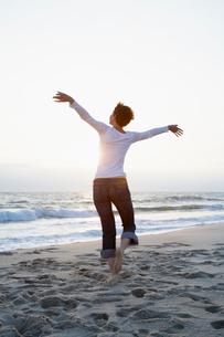 Mid adult woman running on beachの写真素材 [FYI02939779]