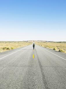 Man walking on centerline of rural roadの写真素材 [FYI02939795]