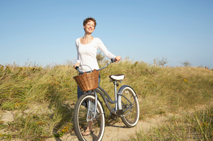 Woman with bicycle walking on pathの写真素材 [FYI02939823]